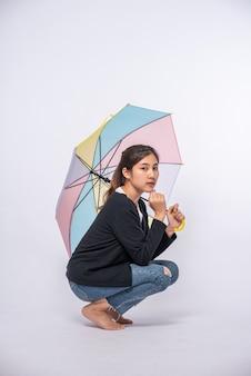 Frau in einem schwarzen hemd, das sitzt und einen regenschirm ausbreitet