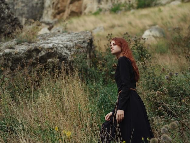 Frau in einem schwarzen kleid liegt auf der grasnaturfreiheitsruhe
