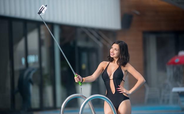 Frau in einem schwarzen sexy badeanzug, selfie foto mit einbeinstativ machend