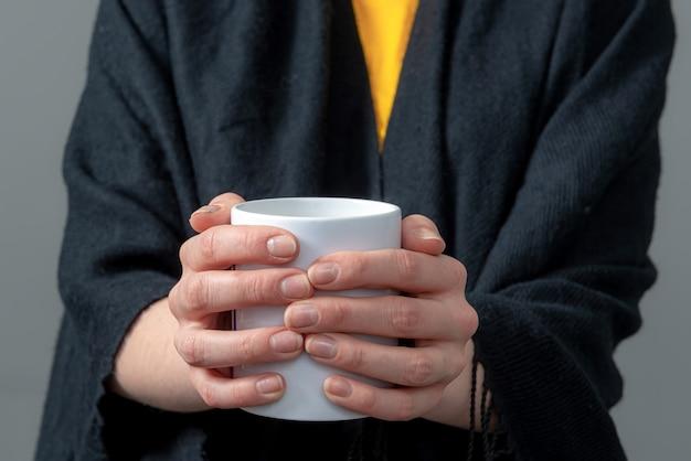 Frau in einem schwarzen umhang hält weißen becher mit heißem getränk in beiden händen, nahaufnahme