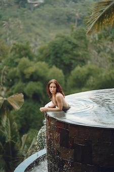 Frau in einem schwimmbad auf einer dschungelansicht