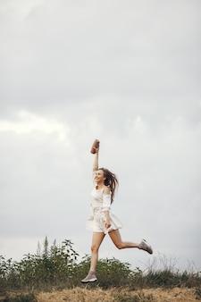 Frau in einem sommerfeld. brünette in einem weißen kleid. mädchen mit musiklautsprecher.