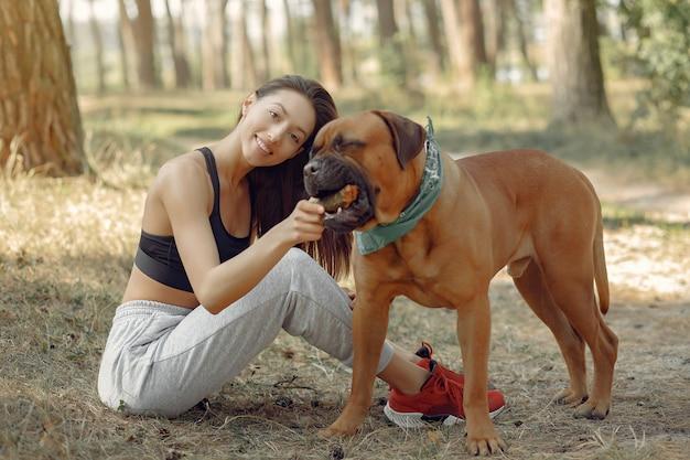Frau in einem sommerwald, der mit hund spielt
