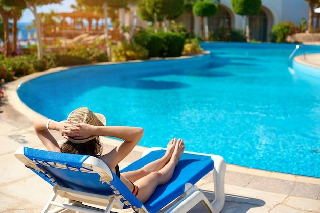 Frau in einem strohhut, der auf einem daybed nahe einem luxuriösen sommerpool sich entspannt