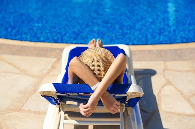 Frau in einem strohhut, der auf einem klappstuhl nahe einem luxuriösen sommerpool im hotel, konzeptzeit sich entspannt zu reisen