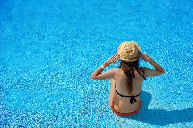 Frau in einem strohhut, der auf einem liegestuhl nahe einem luxuriösen sommerpool im hotel sich entspannt