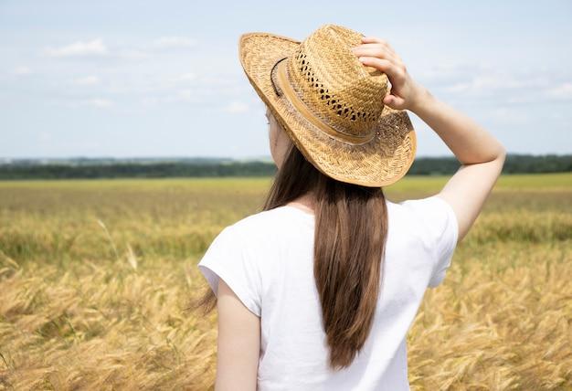 Frau in einem strohhut, der mit dem rücken in der mitte eines weizenfeldes steht und sommerferien auf dem land genießt.