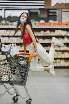 Frau in einem supermarkt. dame in einem beatmungsgerät. mädchen macht parchases.