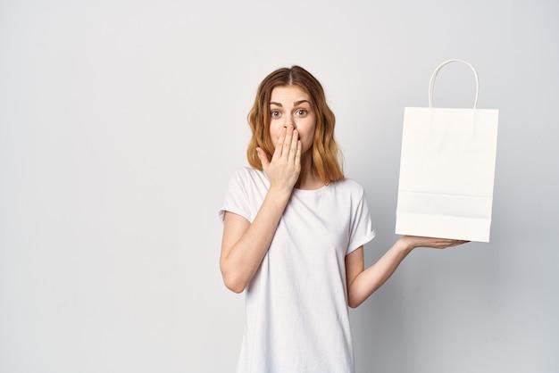 Frau in einem t-shirt-paket in den händen beim einkaufen im laden