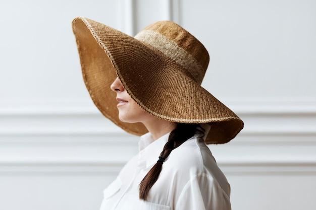 Frau in einem vintage-sommerhut mit breiter krempe