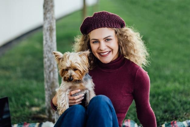 Frau in einem violetten hut bei einem picknick im wald, mit ihrem hund yorkshire terrier. sonnenlicht, helle farbsättigung, einheit mit der natur.