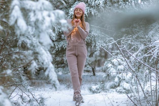 Frau in einem warmen trainingsanzug auf dem hintergrund eines schneebedeckten waldes mit weihnachtsbäumen