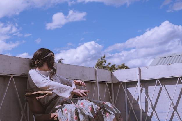 Frau in einem weinlesekleid, das auf dem dach eines gebäudes mit einem schönen blauen himmel und wolken sitzt