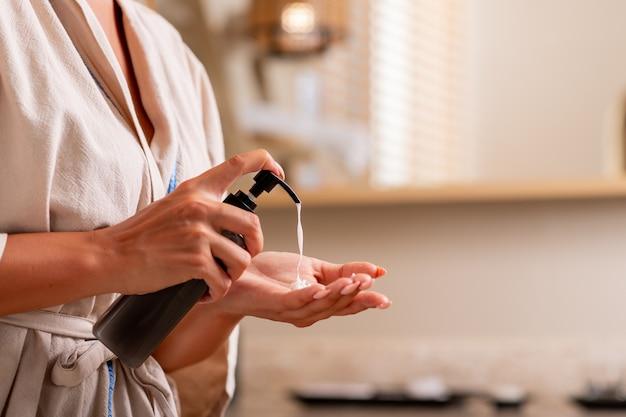 Frau in einem weißen bademantel, der öl aus einer flasche auf ihrer hand quetschend aufwirft.