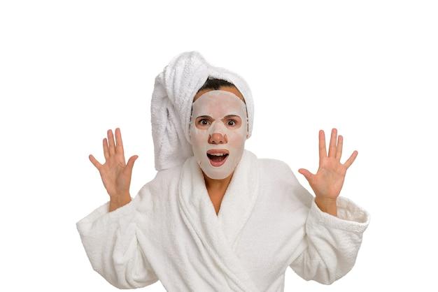 Frau in einem weißen bademantel mit einer feuchtigkeitsspendenden maske im gesicht, die ängstlich in die kamera schaut