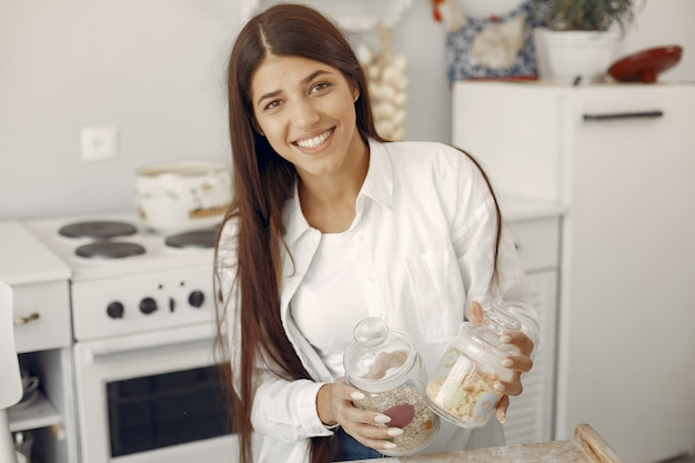 Frau in einem weißen hemd, das in der küche mit hafermehl steht