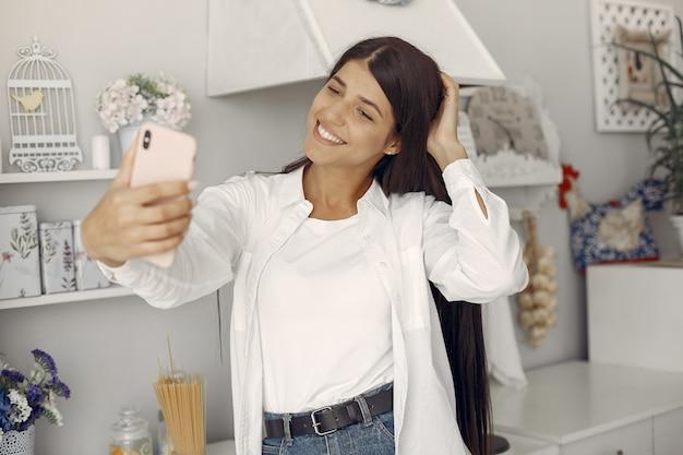 Frau in einem weißen hemd, das in der küche steht und ein selfie macht