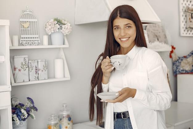 Frau in einem weißen hemd, das in der küche steht und einen kaffee trinkt