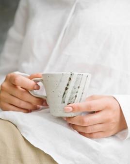 Frau in einem weißen hemd mit einer tasse kaffee auf dem schoß