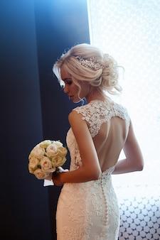 Frau in einem weißen hochzeitskleid, das einen blumenstrauß hält
