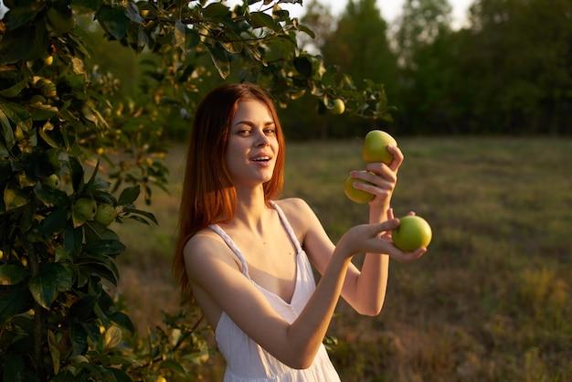 Frau in einem weißen kleid auf einem feld mit äpfeln in den händen