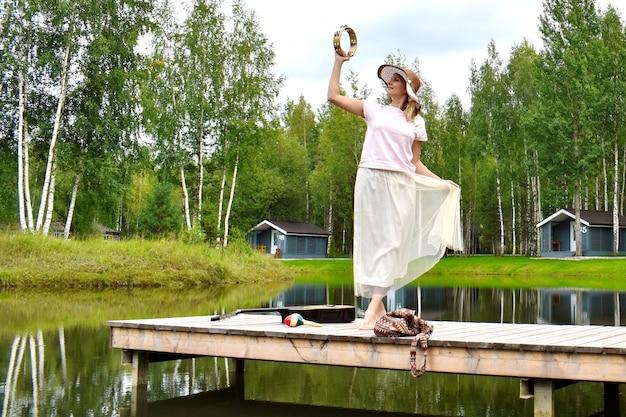 Frau in einem weißen kleid auf einem pier mit einer gitarre