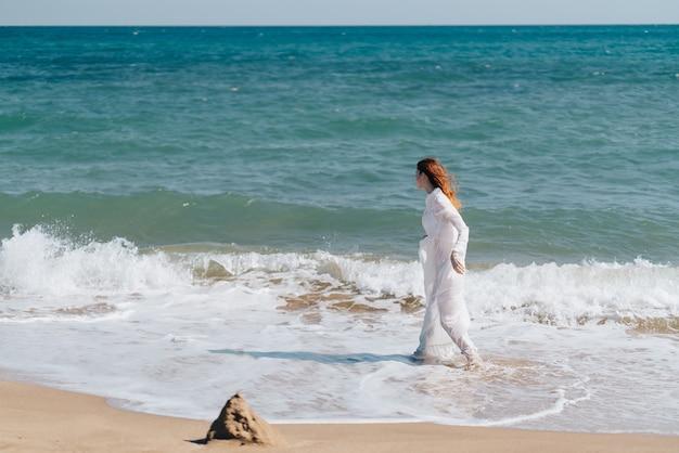 Frau in einem weißen kleid, das auf einem strand geht