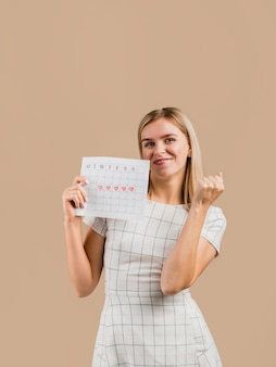 Frau in einem weißen kleid, das ihren menstruationskalender zeigt