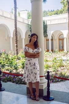 Frau in einem weißen kleid mit blumen steht am eingang der tür zum schloss mit säulen