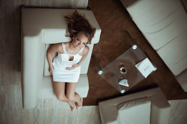Frau in einem weißen kleid sitzt auf einem sofa