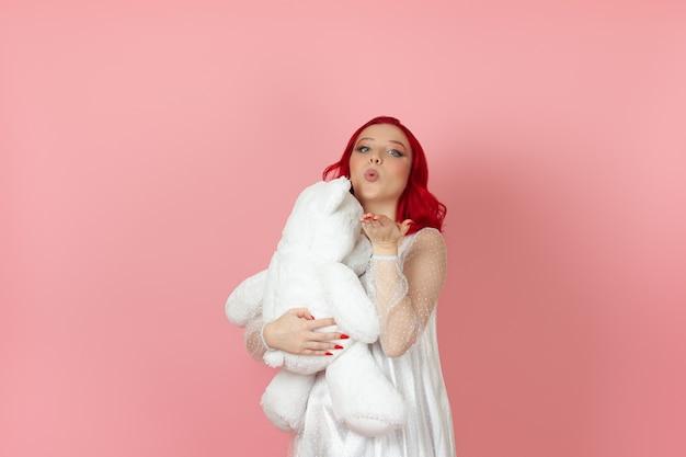 Frau in einem weißen kleid und mit roten haaren bläst einen kuss und umarmt großen weißen teddybär