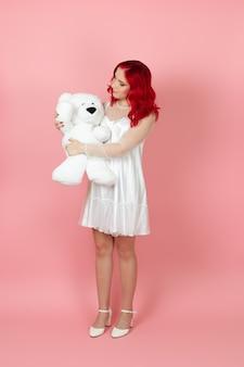 Frau in einem weißen kleid und mit roten haaren hält einen großen weißen teddybär