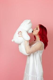Frau in einem weißen kleid und mit roten haaren küsst die nase eines großen weißen teddybären