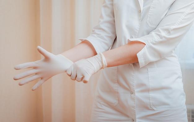 Frau in einem weißen medizinischen kleid zieht gummihandschuhe an