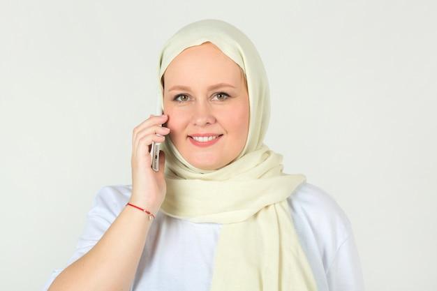 Frau in einem weißen muslimischen kopftuch mit einem telefon in ihrer hand