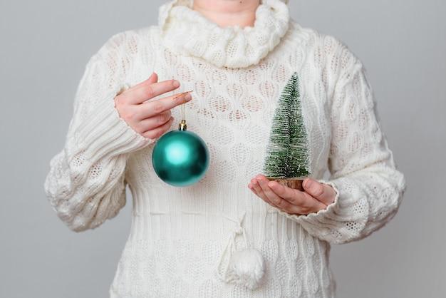 Frau in einem weißen pullover, der eine türkisfarbene weihnachtskugel und eine miniaturkiefer hält