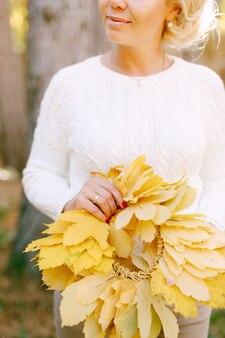 Frau in einem weißen pullover hält einen kranz aus gelbem herbstlaub in ihren händen
