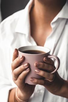 Frau in einem weißen t-shirt hält morgenkaffee in einer rosa keramikschale. maniküre. vorderansicht