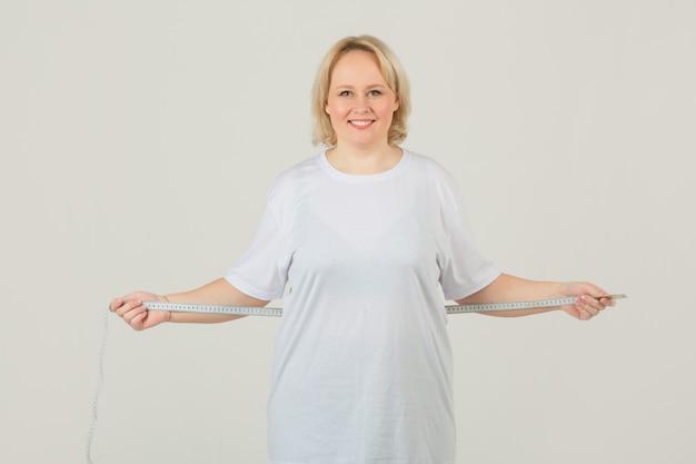Frau in einem weißen t-shirt misst das volumen ihres körpers mit einem maßband
