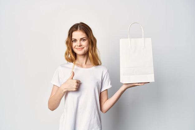 Frau in einem weißen t-shirt mit einem paket in den händen, die mit ihrem handmodell gestikuliert. foto in hoher qualität