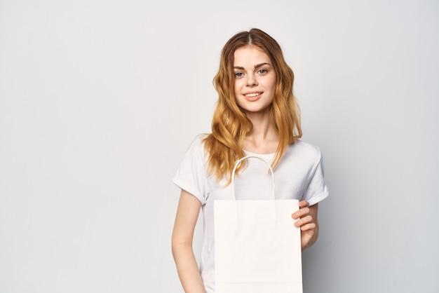 Frau in einem weißen t-shirt mit einem paket in den händen ein geschenk einkaufen heller hintergrund