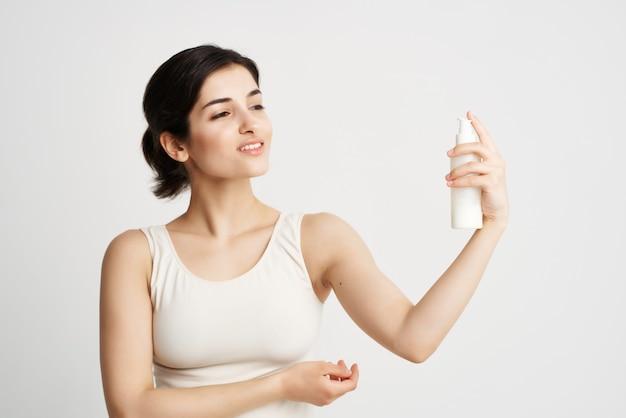 Frau in einem weißen t-shirt setzte sich in ihre hände feuchtigkeitsspendende hautpflege