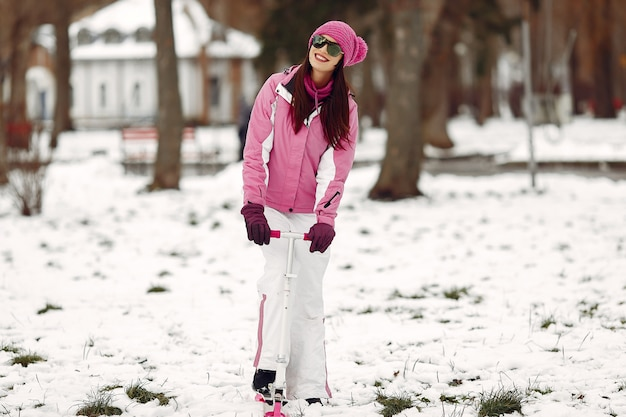Frau in einem winterpark. dame im rosa sportanzug. frau mit schneescooter.