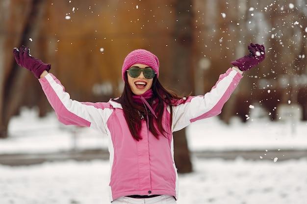 Frau in einem winterpark. dame im rosa sportanzug. mädchen in einer sonnenbrille.