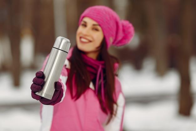 Frau in einem winterpark. dame im rosa sportanzug. mädchen mit einer thermoskanne.