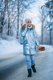 Frau in einem winterpark sprechend am telefon