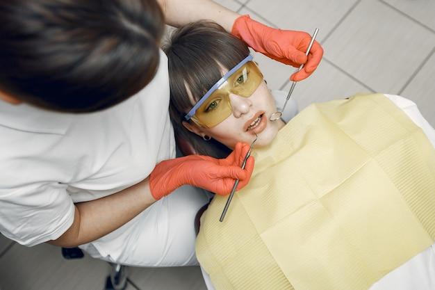 Frau in einem zahnarztstuhl. mädchen wird von einem zahnarzt untersucht. schönheit behandelt ihre zähne