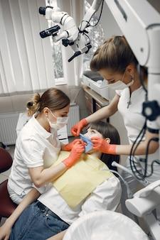 Frau in einem zahnarztstuhl. mädchen wird von einem zahnarzt untersucht. zahnärzte behandeln die zähne eines mädchens