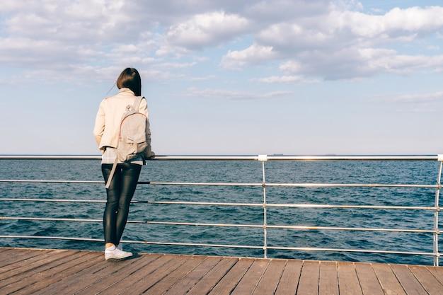 Frau in einer beige jacke und schwarzen hosen steht auf der ufergegend