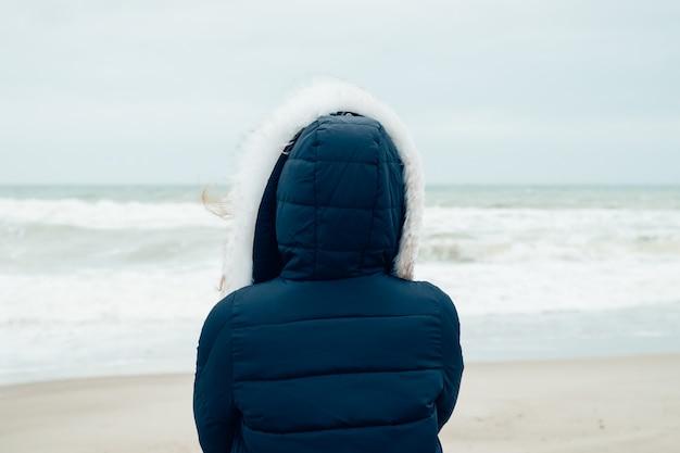 Frau in einer blauen winterjacke mit einer haube steht auf dem winterstrand und betrachtet meer